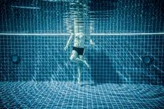 Personas que se colocan debajo del agua en una piscina Fotografía de archivo libre de regalías
