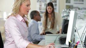 Personas que trabajan en los escritorios en oficina ocupada almacen de metraje de vídeo