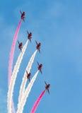 Personas rojas de la visualización de la Royal Air Force de las flechas Foto de archivo libre de regalías