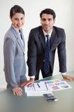 Personas sonrientes de las ventas que estudian sus resultados Fotografía de archivo libre de regalías