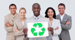 Personas sonrientes del asunto que llevan a cabo un símbolo de reciclaje Fotos de archivo libres de regalías