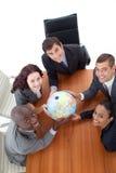 Personas sonrientes que sostienen un globo. Imagen de archivo