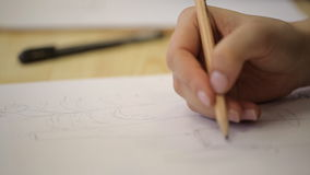 Personattraktioner med blyertspennaflaskor och blommor på arket av papper arkivfilmer