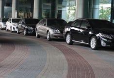Personbilar parkerade framme av byggnad royaltyfria foton