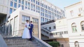 Persone appena sposate che baciano mentre stando sull'orlo delle scale stock footage