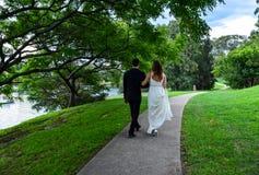 Persone appena sposate che camminano a braccetto immagine stock
