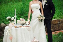 Persone appena sposate che stringono a sé vicino alla tavola sveglia con i dolci fotografia stock