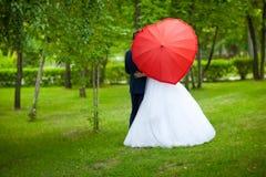 Persone appena sposate con l'ombrello sotto forma di un cuore Fotografie Stock