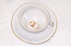 Persone appena sposate degli anelli di oro e tazza bianca vuota Fotografie Stock