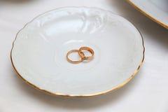 Persone appena sposate degli anelli di oro e tazza bianca vuota Fotografia Stock