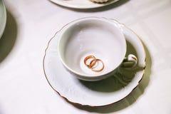 Persone appena sposate degli anelli di oro e tazza bianca vuota Immagini Stock Libere da Diritti
