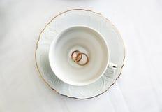 Persone appena sposate degli anelli di oro e tazza bianca vuota Fotografie Stock Libere da Diritti