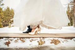 Persone appena sposate delle gambe sul ponte di legno nelle nozze di inverno Fotografie Stock