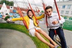 Persone appena sposate emozionali che gridano mentre guidando sull'alto carosello in parco di divertimenti Coppie espressive di n Fotografie Stock Libere da Diritti
