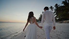 Persone appena sposate felici al tramonto vicino all'oceano Camminano a piedi nudi lungo la riva, tenersi per mano e lo sguardo s video d archivio