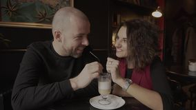 Persone appena sposate felici delle coppie che si siedono in un caffè ed in un latte bevente da una tazza stock footage