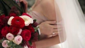 Persone appena sposate sposo e bacio e colpo dell'abbraccio della sposa in foresta sempreverde nevosa durante le precipitazioni n video d archivio