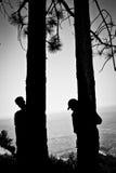 2 persone che si nascondono negli alberi Immagine Stock