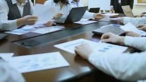 Persone di affari che dividono i documenti alla riunione, funzionamento sui computer portatili, cooperazione video d archivio