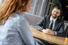 Persone di affari che hanno pranzo di lavoro all'uomo di seduta del ristorante che esamina sorridere della donna allegro fotografie stock