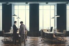 Persone di affari che parlano in un ufficio grigio, tonificato Fotografie Stock Libere da Diritti