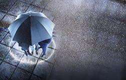 Persone di affari che riparano sotto un ombrello in pioggia Fotografia Stock