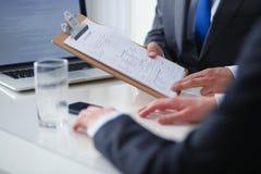 Persone di affari che si siedono sullo scrittorio sull'ufficio businesspeople Immagini Stock
