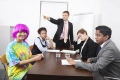Persone di affari multietniche arrabbiate con il collega in parrucca rosa alla riunione immagini stock