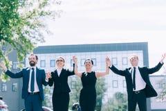 Persone di affari multietniche che si tengono per mano mentre stando insieme fuori Fotografia Stock Libera da Diritti