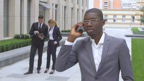 Persone di affari multirazziali di successo Afroamericano che parla sul telefono stock footage
