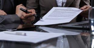 Persone di affari o avvocati che firmano contratto alla riunione Primo piano delle mani umane sul lavoro Illuminazione scura Fotografia Stock