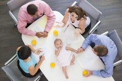 Persone di affari in sala del consiglio con un bambino sulla tabella Fotografie Stock