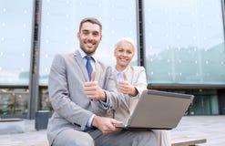 Persone di affari sorridenti con il computer portatile all'aperto Immagini Stock