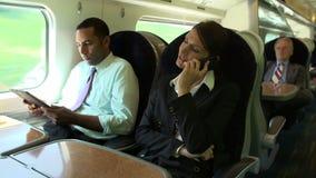 Persone di affari sul treno facendo uso dei dispositivi di Digital video d archivio