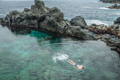 Persone dive in the natural swimming pool Charco De La Laja. At the north of Tenerife, Canary Islands, Spain Stock Photo