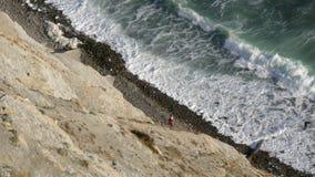 2 persone nel rosso stanno camminando lungo la costa e sono nascoste dalla vista dietro la montagna video d archivio