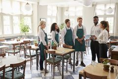 Personeel die Team Meeting In Empty Dining-Zaal bijwonen stock afbeeldingen