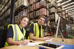 Personeel in het bureau van een distributiepakhuis, aan camera stock fotografie