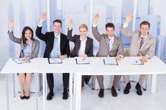 Personeelsambtenaren die die met handen zitten bij lijst worden opgeheven royalty-vrije stock afbeelding