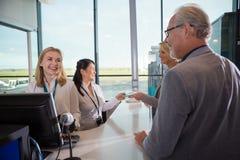 Personel Patrzeje pasażerów Przy kontuarem W lotnisku Obrazy Royalty Free
