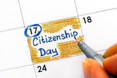 Personen fingrar med dag för medborgarskap för pennhandstilpåminnelse i cale arkivfoto