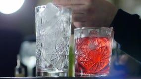 Personen häller kväv ut i exponeringsglas med is, och near är livligt ordnar till drinken arkivfilmer