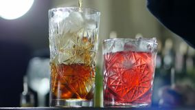 Personen häller ut alkohol i exponeringsglas med is, och near är den ljusa klara coctailen arkivfilmer