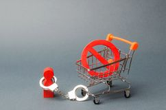 personen handfängslas till ett symbol INTE på en supermarketvagn En person begränsas av lagar, regler och traditioner censur fotografering för bildbyråer