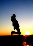 Personen hoppar i solnedgång Arkivbild