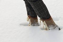 Personen i kängor går på en djup snö Arkivfoto