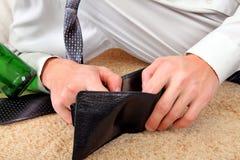 Personen kontrollerar plånboken Arkivbild
