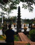 Personen-Sitzen am Hauptbrunnen bei Tirta Gangga, Bali stockfotografie