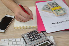 Personen som pekar handstilmål på ett papper, handstilaffärsplan på arbetsplatsen, man hållande pennor, legitimationshandlingar,  Arkivfoto