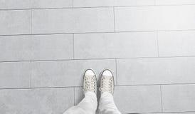 Personen som tar fotoet av hans, foots ställningen på tomt golv Royaltyfri Foto